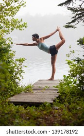 middle aged woman practicing yoga, standing bow pose, on dock by a lake in the foggy morning, vertical composition, Surry Maine