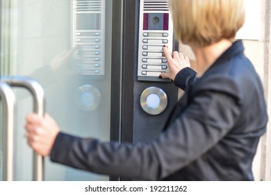 Middle aged woman pushing button of intercom