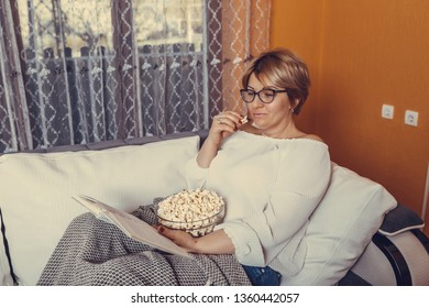 Middle aged woman reading book and eating popcorn while sitting on the couch at home - Image