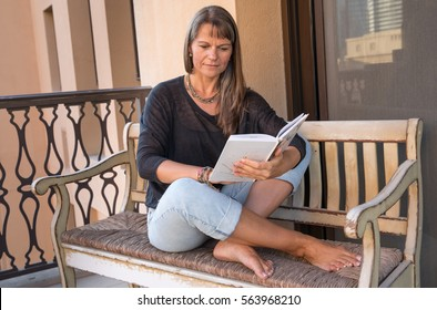 Middle aged woman reading a book on a balcony.