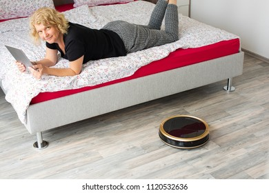 A middle aged woman is reading on her digital tablet on her bed while her vaccum cleaning robot is cleaning the wooden floor at home. Household, leisure and technology concept