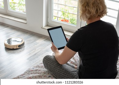 A middle aged woman is reading on her digital tablet on her bed while her vaccum cleaning robot is cleaning the wooden floor at home. Blank screen with space for your text, website or message on the