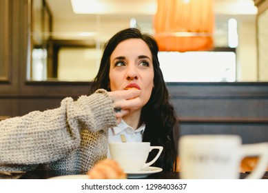Middle aged woman, real people, eating a croissant with coffee in a coffee shop.