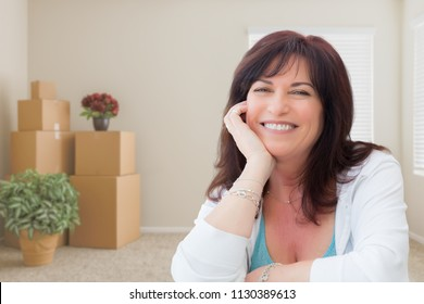 Middle Aged Woman Relaxing Inside Empty Room With Moving Boxes.