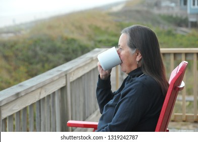 Middle aged woman relaxing on a beach front deck sipper her morning coffee