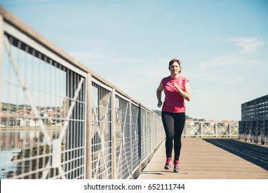 Middle aged woman running outdoors in a sunny and hot day