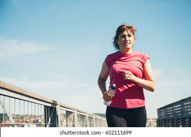 Middle aged woman running with a water bottle in hand in a sunny and hot day