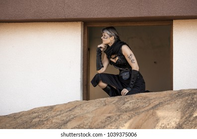 Middle Aged Woman in a sexy black Steampunk Warrior outfit sitting over the window of her destroyed house contemplating devastation