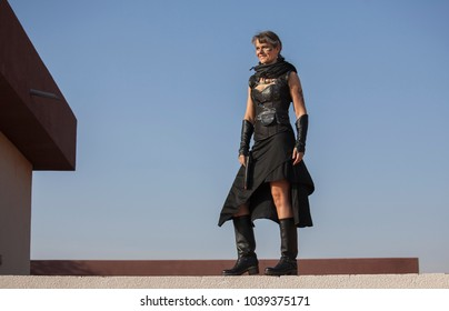 Middle Aged Woman in a sexy black Steampunk Warrior outfit standing over the wall of her destroyed house contemplating devastation