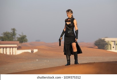 Middle Aged Woman in a sexy black Steampunk Warrior outfit holding a gun and looking at the devastation around her