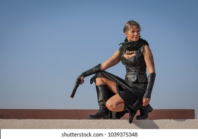 Middle Aged Woman in a sexy black Steampunk Warrior outfit sitting over the wall of her destroyed house contemplating devastation