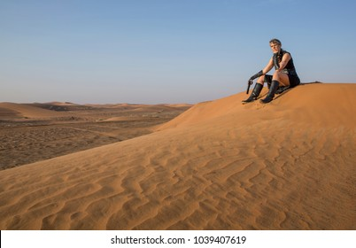 Middle Aged Woman in a sexy black Steampunk Warrior outfit sitting over a dune of her destroyed village contemplating devastation