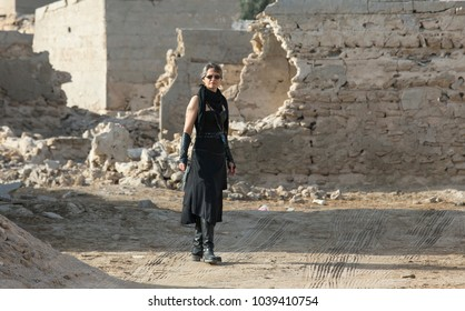 Middle Aged Woman in a sexy black Steampunk Warrior outfit roaming around her destroyed village and shooting at enemies