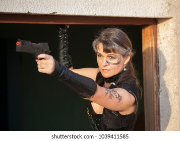 Middle Aged Woman in a sexy black Steampunk Warrior outfit holding a gun and aiming at enemies