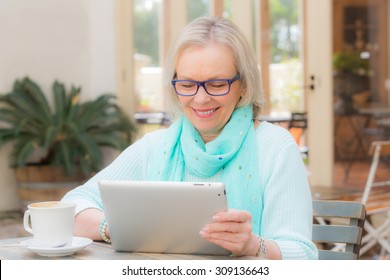 Middle aged woman sits at cafe while using a tablet computer