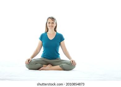Middle aged woman sitting in crosslegged position. Yoga. Meditation