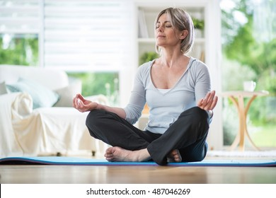 Middle aged woman sitting in lotus position on a carpet in his living room. her eyes are closed. she is in the foreground, the focus is on it. in the background, the garden is blur