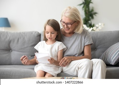 Middle aged woman sitting on couch at home with little girl. Loving grandma teaching adorable preschool grandchild reading or counting numbers or to draw. Education and development of child concept