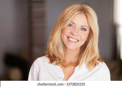 Middle aged woman smiling at the camera at home. White