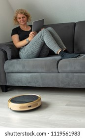 Middle aged woman is steering her vacuum cleaning robot using a digital tablet while resting on the sofa