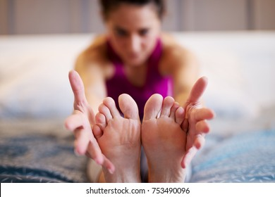 Middle aged woman stretching yoga exercise while sitting forward on the bed while her hands are holding the feets. Focus on the feets and hands.