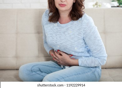 Middle aged woman suffering from abdominal pain while sitting on bed at home