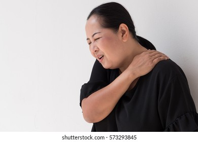middle aged woman suffering from shoulder pain, muscle issue, stiffness
