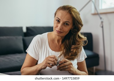 middle aged woman taking medicine pills at her home
