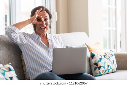 Middle aged woman using laptop in the sofa with happy face smiling doing ok sign with hand on eye looking through fingers