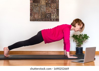Middle aged woman watching yoga exercises online video tutorial and trying to do Phalankasana pose.