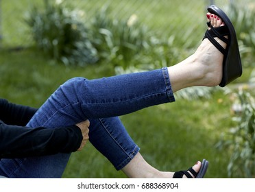 A middle aged woman wearing jeans and sandals holding leg up under the knee to stretch it