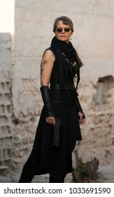 Middle Aged Woman Wearing steampunk costume of freedom Fighter in her old  destroyed village