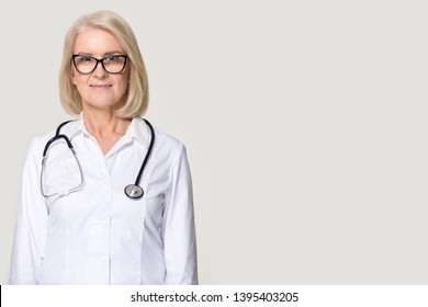 Middle aged woman wearing white coat stethoscope on shoulders posing on grey studio background, female doctor or nurse standing aside copy space for clinic advertisement services medical care concept