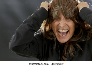 Middle aged woman yelling with mouth open, eyes closed tightly and hands grabbing her hair in an upset motion