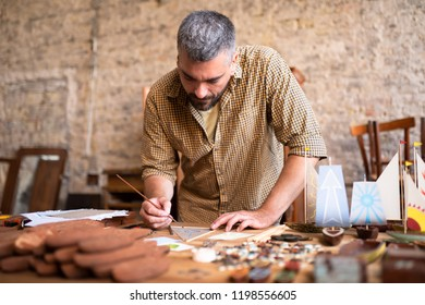 Middle aged wood carpenter works on his project. Concentrated joiner draws his future models.