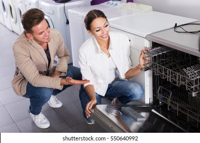 Middle class family selecting modern dishwasher in hypermarket and smiling
