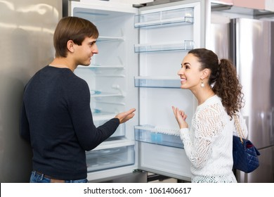 Middle class spanish family couple choosing new refrigerator in hypermarket