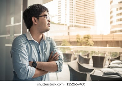 middle class working age casual outfit with glasses standing near office work place window glass look outside with hopeful eyes think about business and future of his career