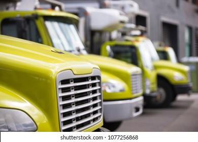 Middle class yellow semi trucks different makes and models with refrigerator unit on box trailers for moving and delivery services standing in row in warehouse dock waiting for customers