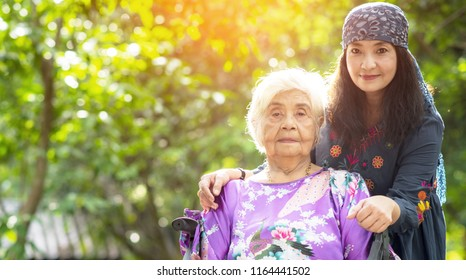 Middle daughter and elderly mother.Grandmother and granddaughter. Young woman carefully takes care of an older woman.
