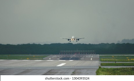 Middle distance shot of twin engine commercial airplane approaching to landing in airport