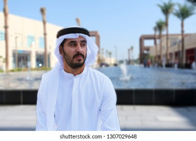Middle East Arab man sitting outdoors with copy space ideal for marketing campaign wearing arabic menswear kandura
