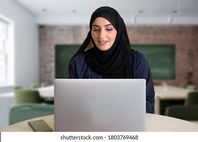 Middle East Arab student using laptop computer while doing her research paperwork with blurred school classroom with blackboard and table chairs as background