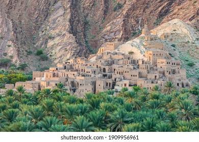 Middle East, Arabian Peninsula, Oman, Ad Dakhiliyah, Nizwa. Palm trees and a traditional mountain village in Nizwa,Oman.