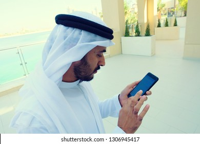Middle East Arabic man using mobile phone touch screen doing online banking or eCommerce purchase