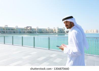 Middle East Arabic Man walking on bricks wearing thawb kandura