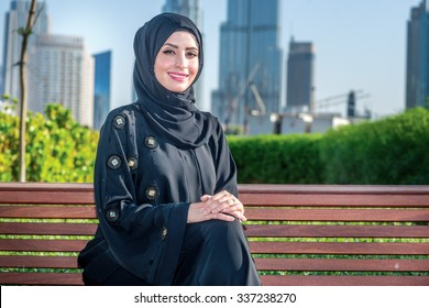 Middle east business. Arab businesswomen in hijab sitting on the bench on the background of skyscrapers in Dubai while smiling at the camera. The woman is dressed in a black abaya