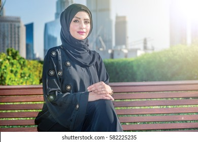 Middle east business. Arab businesswomen in hijab sitting on the bench on the background of skyscrapers in Dubai while smiling to the side. The woman is dressed in a black abaya