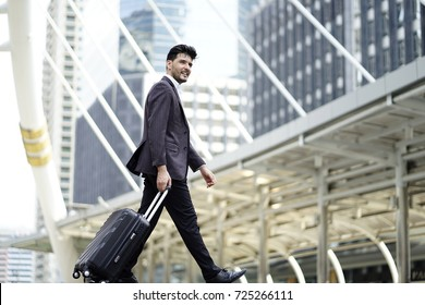 Middle East businessman with suit and suitcase on business trip. Man walking outdoors with luggage in the routine working with determination and confidence. concept of trip travel and transportation.