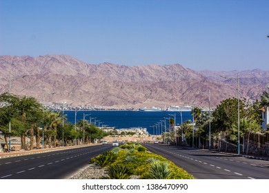 Middle East city view car road way down to Gulf of Aqaba Red sea bay waterfront district, palm trees alley on both sides, bare desert mountain ridge horizon background in Jordan country